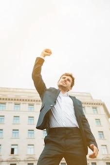 Lage hoekmening van een zakenman die zijn succes viert