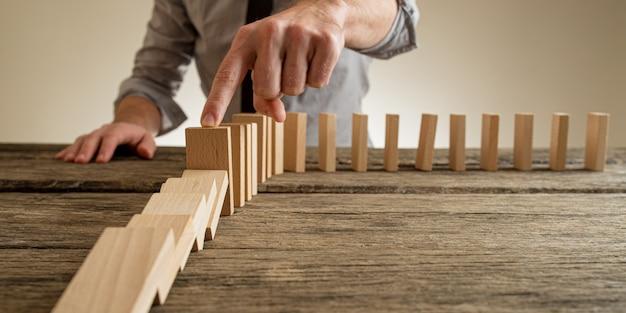 Lage hoekmening van een zakenmanvinger die instortende dominostenen stopt in een conceptueel beeld van bedrijfscrisisbeheer.