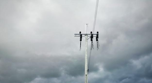 Lage hoekmening van elektrische paal en kabels tegen donkere bewolkte stormachtige hemel