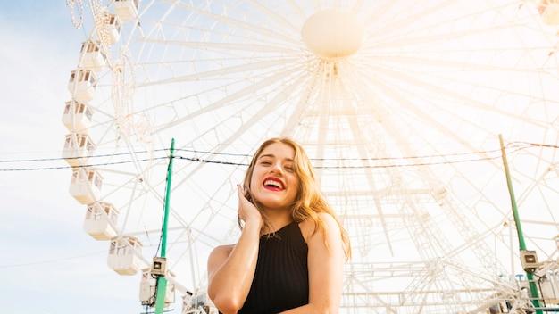 Lage hoekmening van gelukkige jonge vrouw die zich voor groot reuzewiel bevindt