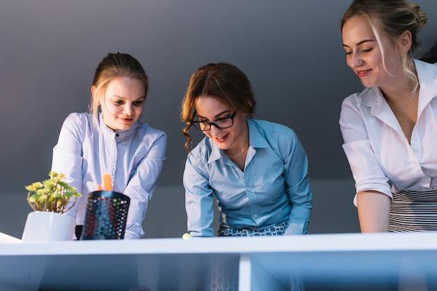 Lage hoekmening van glimlachende onderneemster die aan bureau in het bureau werken