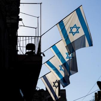 Lage hoekmening van israëlische vlaggen op het inbouwen van de oude stad van jeruzalem, israël