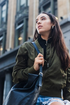 Lage hoekmening van jonge vrouw die blauwe handtas houdt lopend in de straat