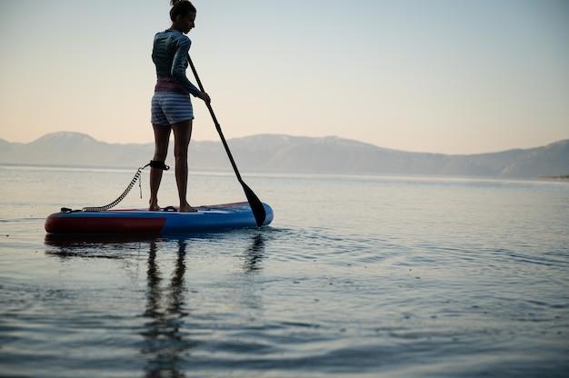 Lage hoekmening van jonge vrouw die vroeg in de ochtend traint, peddelen op sup board drijvend op kalm zeewater.