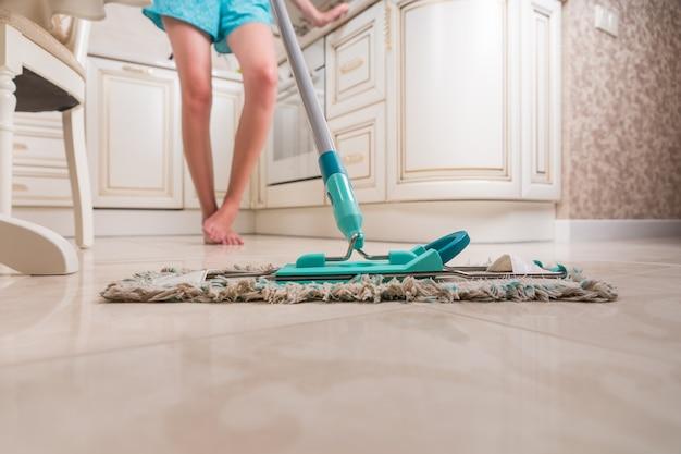 Lage hoekmening van jonge vrouw keukenvloer dweilen met focus op glanzende schone vloer en dweil