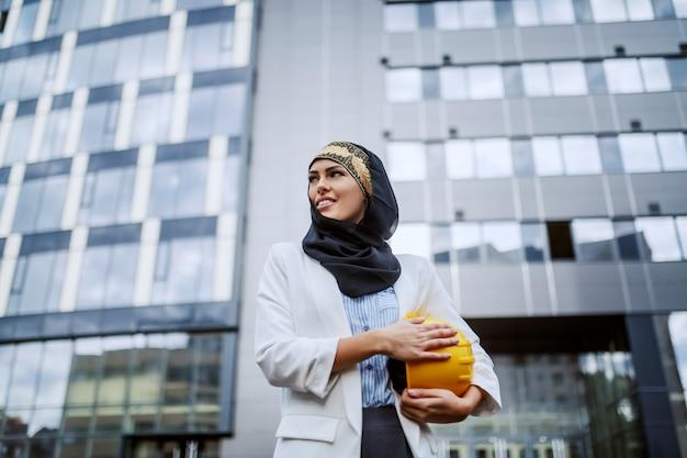 Lage hoekmening van prachtige succesvolle glimlachende positieve vrouwelijke moslimarchitect die voor haar firma met helm onder oksel staat.