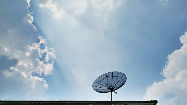 Lage hoekmening van satellietontvanger dish op het dak tegen blauwe bewolkte hemel
