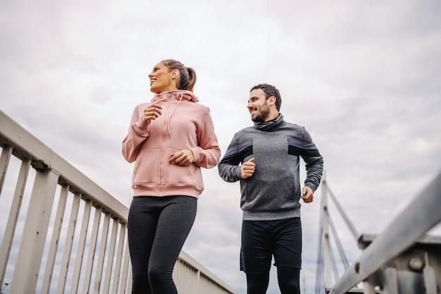 Lage hoekmening van toegewijde jonge heteroseksuele sportieve vrienden in sportkleding draait op de brug en prachtig uitzicht te kijken. stedelijk exterieur. fitness buitenshuis concept.