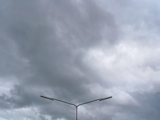 Lage hoekmening van verlichtingspost tegen donkere bewolkte hemel