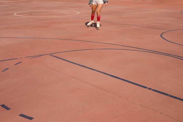 Lage hoekmening van vrouwelijke skater die op hof schaatst