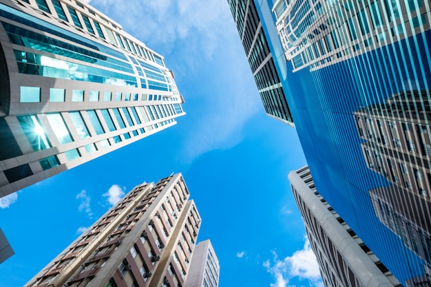 Lage hoekmening van wolkenkrabbergebouwen met glasvensters en blauwe hemel