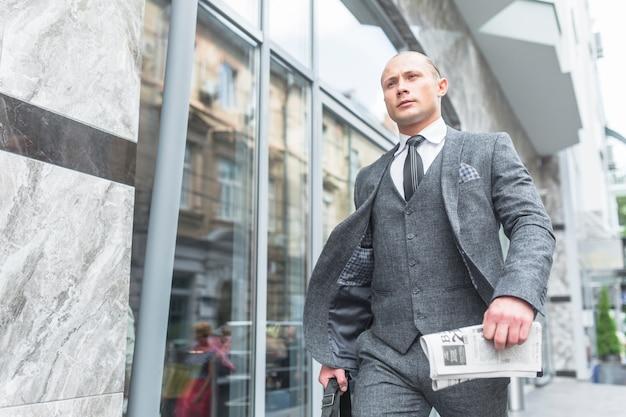 Lage hoekmening van zakenman in kostuum die door glasvenster overgaan