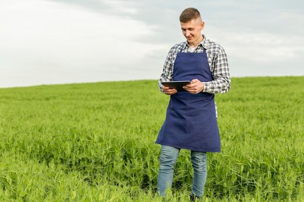 Lage hoekmens bij landbouwbedrijf met tablet