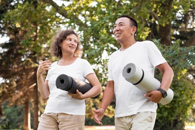 Lage hoekmensen die yogamatten houden