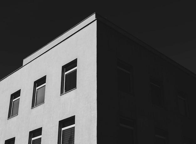 Lage hoekopname in grijstinten van een betonnen gebouw met veel ramen onder de donkere lucht