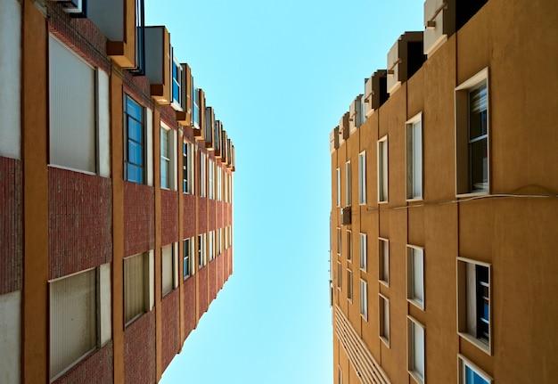 Lage hoekopname van appartementsgebouwen tegen heldere hemelachtergrond