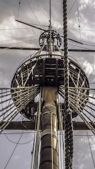 Lage hoekopname van de hoofdmast van een schip onder de bewolkte hemel