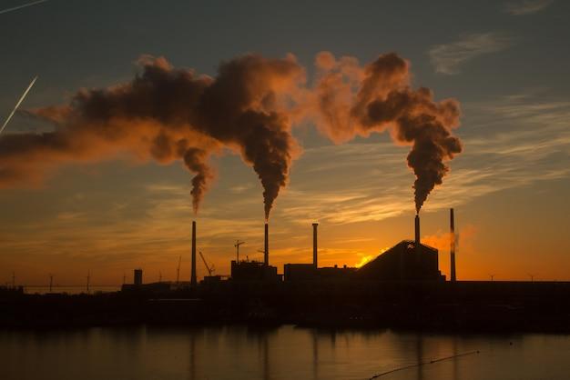Lage hoekopname van een fabriek met rook en stoom die uit de schoorstenen komen, vastgelegd bij zonsondergang