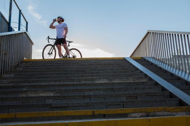 Lage hoekopname van een mannelijke gespierde fietser die water drinkt, op zomerdag bij zijn fiets staat, kopieer ruimte