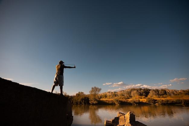 Lage hoekopname van een mannetje dat bij zonsondergang met een katapult speelt