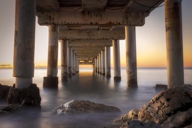 Lage hoekopname van een pier in marbella, spanje tijdens zonsopgang