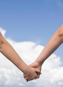 Lage hoekopname van twee mensen die elkaars hand vasthouden - vriendschap, liefdesconcepten