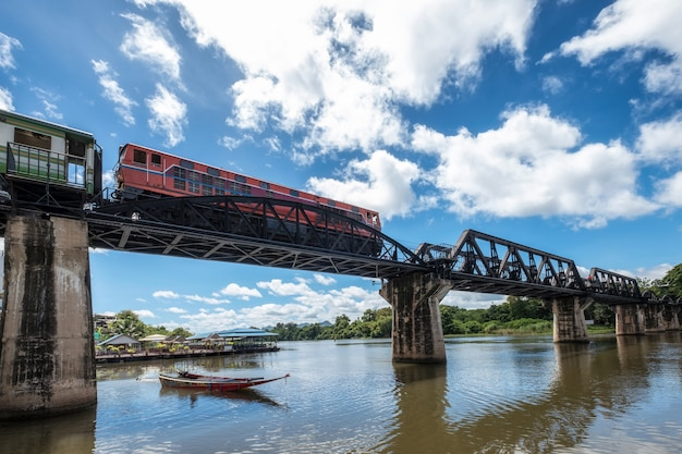 Lage hoektrein die op histotic spoorweg van de brug van rivierkwai in kanchanaburi loopt