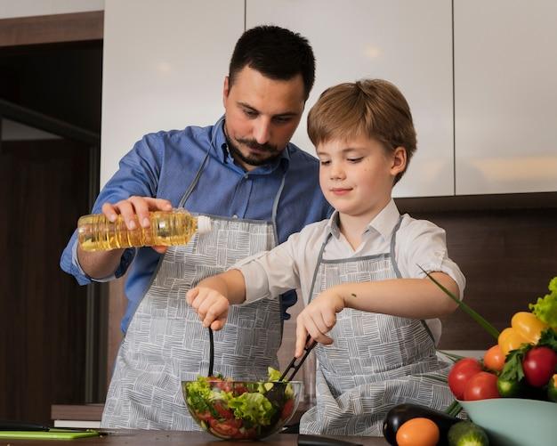 Lage hoekvader en zoon die salade maken