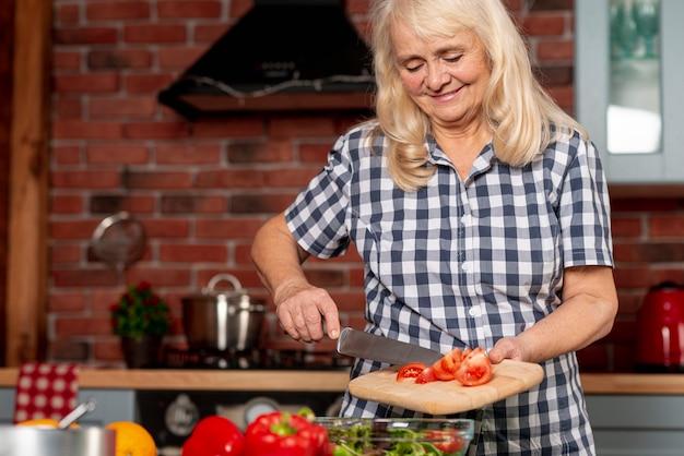Lage hoekvrouw die gezond voedsel kookt