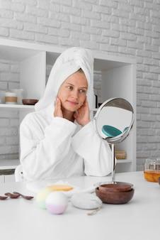 Lage hoekvrouw die in de spiegel kijkt