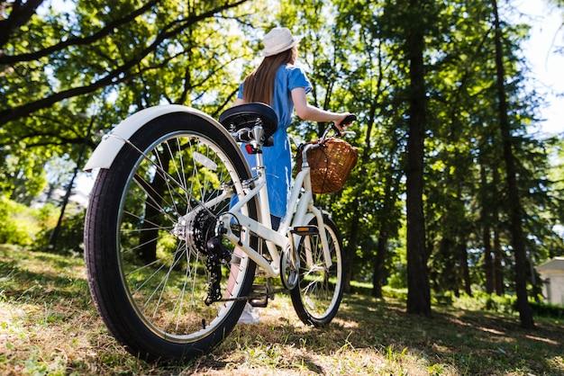Lage hoekvrouw die met fiets loopt
