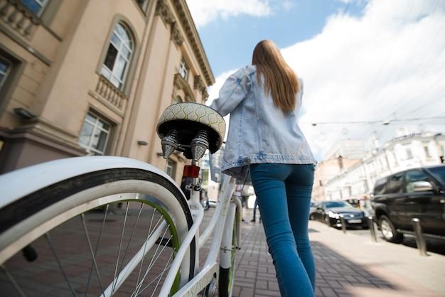 Lage hoekvrouw die naast fiets loopt