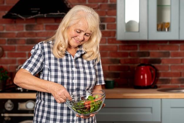 Lage hoekvrouw die salade mengt