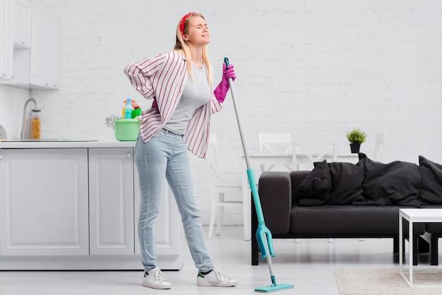 Lage hoekvrouw die thuis schoonmaakt