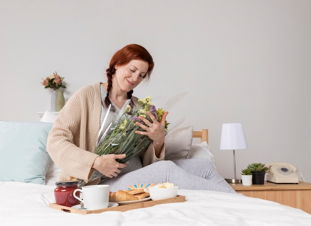 Lage hoekvrouw met bloemenboeket