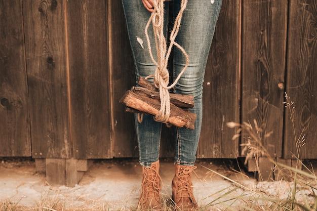 Lage kijkende vrouw die brandhout draagt