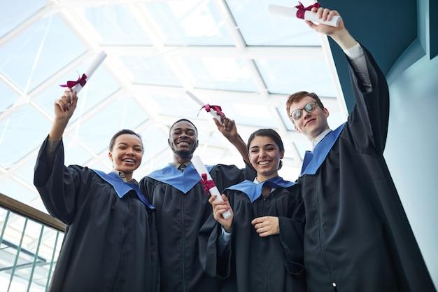 Lage kijkhoek op zicht op diverse groep vrolijke jonge mensen die afstudeerjurken dragen en naar de camera glimlachen terwijl ze diplomacertificaten omhoog houden