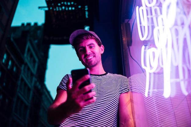 Lage mening van de mens die zijn telefoon en glimlach bekijkt