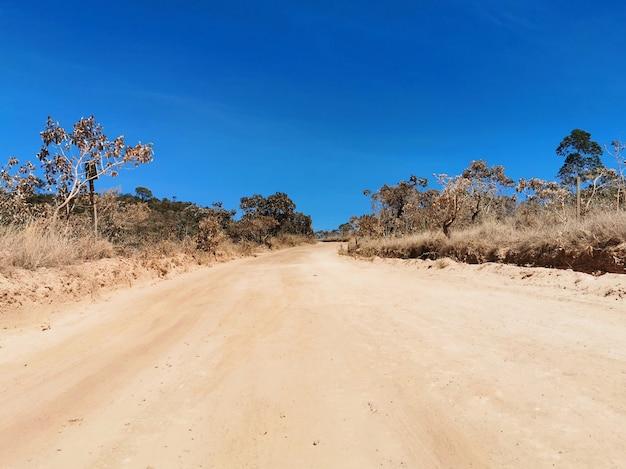 Lage mening van onverharde weg met blauwe hemel bij chapada dos veadeiros