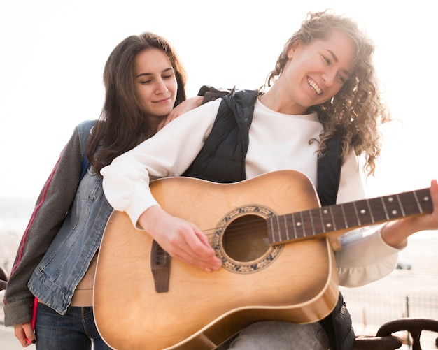 Lage mening vrouwelijke vrienden die gitaar spelen