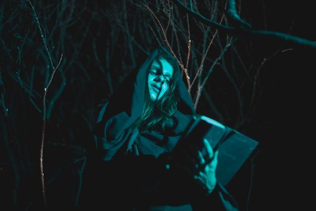 Lage meningsmens die een lantaarn en een boek in de nacht houdt