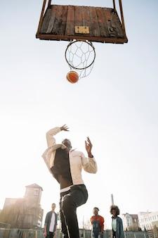 Lage meningsvrienden die basketbal in openlucht spelen