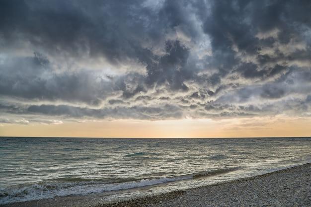 Lage onweerswolken zweven boven de zee en onthullen een zonsondergang