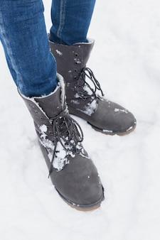 Lage sectie die van vrouw zich met de winterlaarzen in sneeuw bevindt