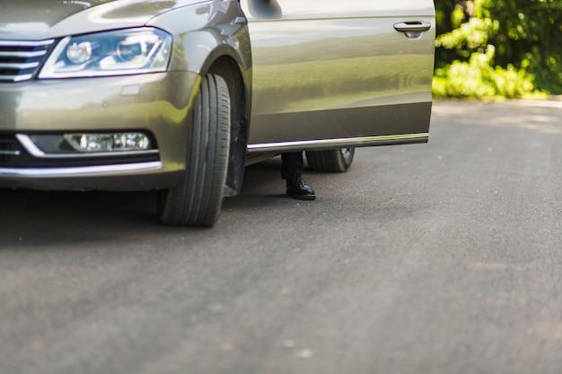 Lage sectie van de voet van een man achter de open deur van de auto