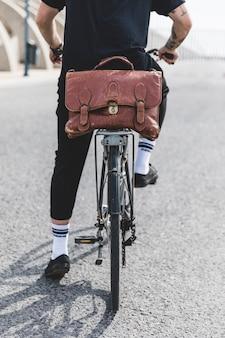 Lage sectie van een jonge mens die de fiets berijdt op weg