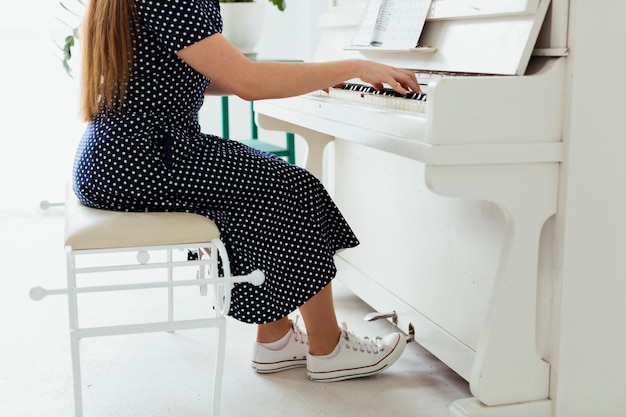 Lage sectie van een jonge vrouw die canvasschoenen draagt die de piano spelen