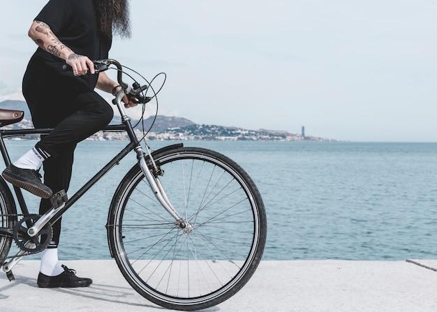 Lage sectie van een mens die de fiets berijdt op straat dichtbij de haven