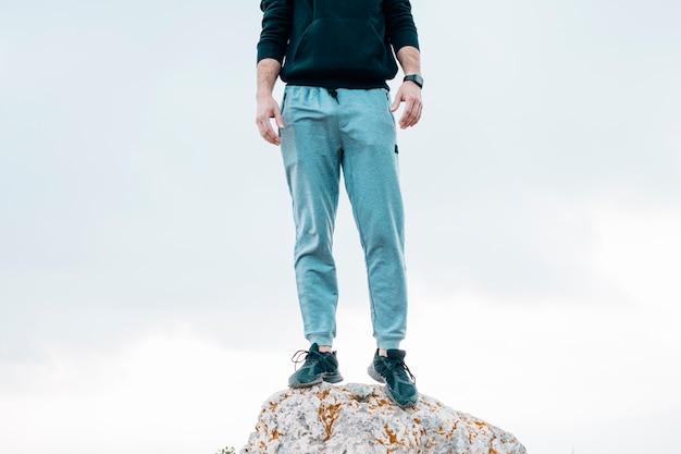 Lage sectie van een mens die zich op rots tegen blauwe hemel bevindt