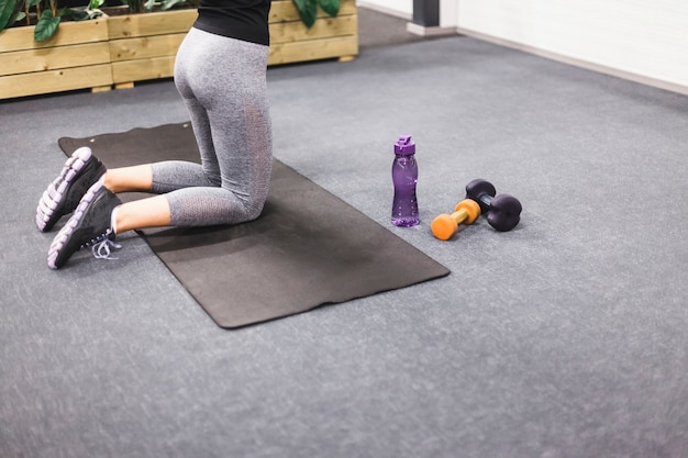 Lage sectie van een vrouw die oefening op yogamat doet